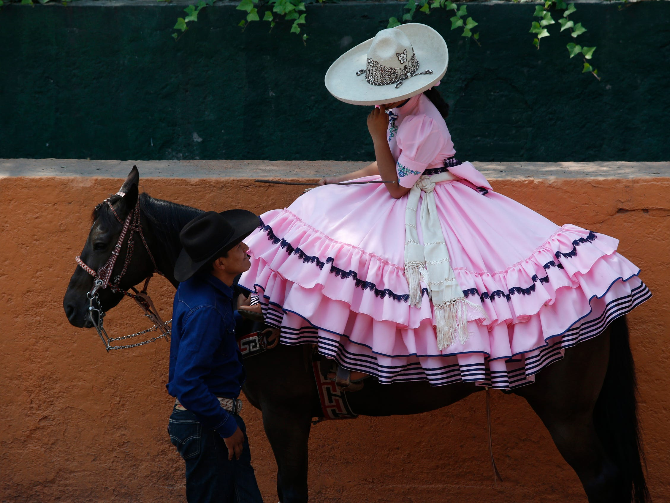 A cowboy chats with an Escaramuza before her presentation at the Rancho del Charro on the outskirts of Mexico City, Mexico, Saturday, May 18, 2019. Mexico's Charros National Association is marking their 98th anniversary, celebrated from May 15 -June 2.