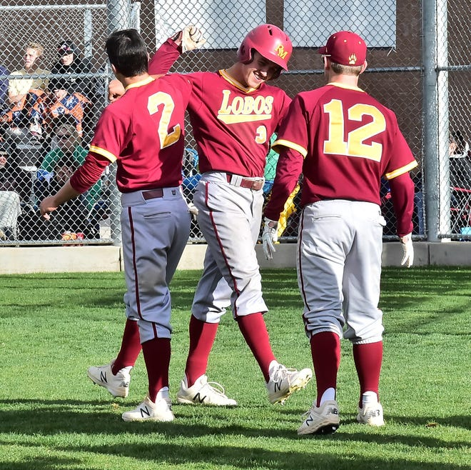 Rocky Mountain High School baseball player Jett Hoggatt is congratulated by teammates Dylan Hupfer (2) and Cooper Axe (12) after scoring a run in a Class 5A regional championship win May 18, 2019, over host Legend High School in Parker. Hoggatt and the Lobos are participating in the state tournament this weekend and will play an elimination game at 9:30 a.m. Saturday at All City Stadium in Denver. Win, and the Lobos will play at least one more game Saturday. Lose, and they're out of the tournament.