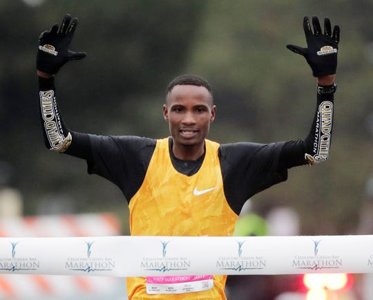 Panuel Mkungo wins the men's race in the Cellcom Green Bay Half Marathon on Sunday.