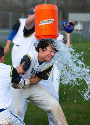 Oconto teammates shower Andrew Ramage with praise after scoring the walk-off run in the May 14 game with Algoma.