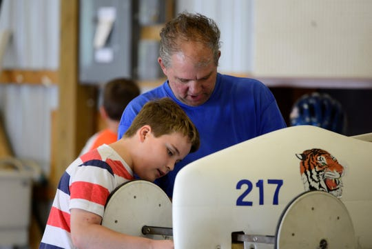 Joshua Laux, left, and Shawn Laux tag-team the construction of a soap box car ahead of the the North Central Ohio Soap Box Derby.