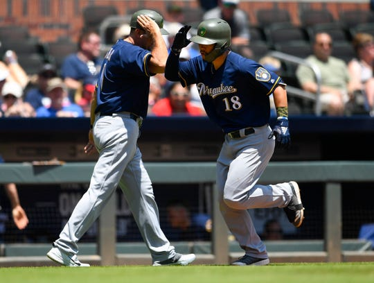 Milwaukee Brewers' Keston Hiura (18) celebrates his home run to left field with third base coach Ed Sedar during the fifth inning of a baseball game against the Atlanta Braves, Sunday, May 19, 2019, in Atlanta. (AP Photo/John Amis)