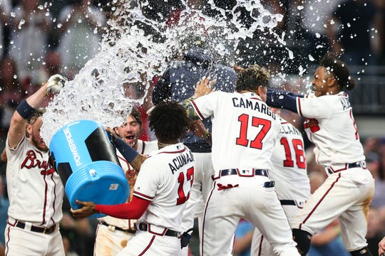 Braves players celebrate Freddie Freeman's walk-off homer Saturday night at SunTrust Park.