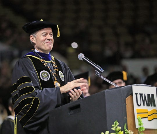 UW-Milwaukee Chancellor Mark Mone applauds the graduates during his remarks.