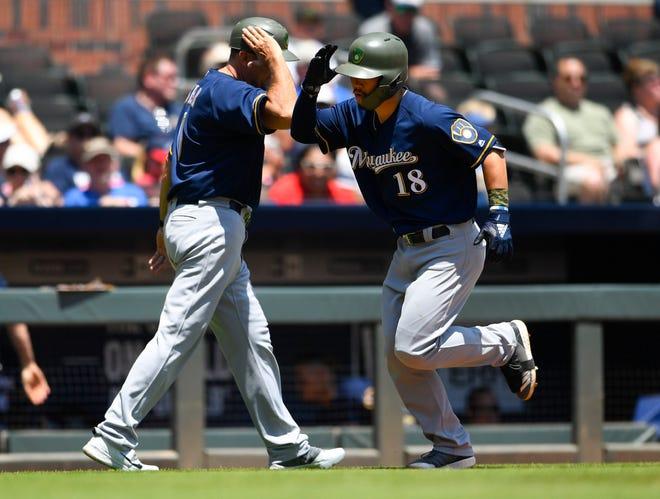 Brewers second baseman  Keston Hiura celebrates his home run to left field with third base coach Ed Sedar.