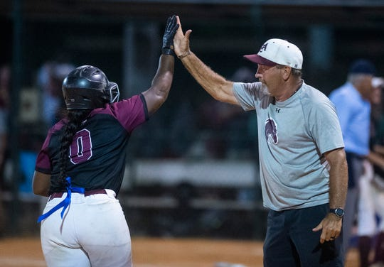 Alabama Christian's Aniya Jackson high fives Alabama Christian coach Chris Goodman as she rounds the bases after hitting the go-ahead home run to beat Rogers to win the AHSAA 4A State Softball Championship at Lagoon Park in Montgomery, Ala., on Saturday May 18, 2019.