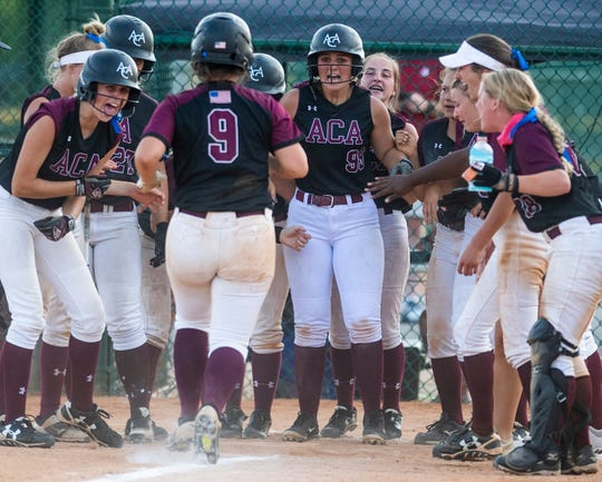 Alabama Christian's Monica Willingham (9) is greeted at home plate by teammates after hitting a grand slam home run against Rogers during the AHSAA Softball Championships at Lagoon Park in Montgomery, Ala., on Saturday May 18, 2019.