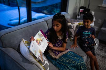 Aleena Ali reads to friends and family about Ramadan before dinner