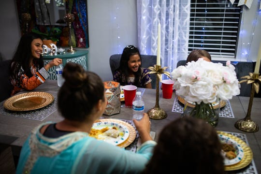 Aleena Ali, center, eats with her friends at her home in Naples on Saturday, May 18, 2019. The Ali family, who moved to Naples from California 3 years ago, hosted the meal for friends, family, and neighbors in their community.
