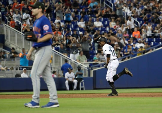 Miami Marlins' Curtis Granderson, right, rounds the bases after hitting a solo home run off of New York Mets relief pitcher Seth Lugo, left, in the eighth inning during a baseball game, Sunday, May 19, 2019, in Miami. (AP Photo/Lynne Sladky)