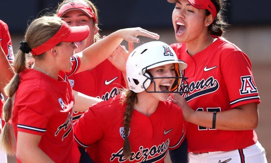 Arizona's Tamara Statman is surrounded by her teammates after slashing a two-RBI single against Auburn in the fourth inning during their NCAA Regional game at Hillenbrand Stadium on Friday. The two runs were all the Wildcats needed in a 2-1 win.
