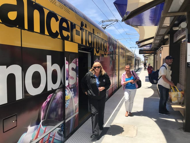 Passengers exit a light-rail train at the new station at Gilbert Road and Main Street on May 18, 2019.