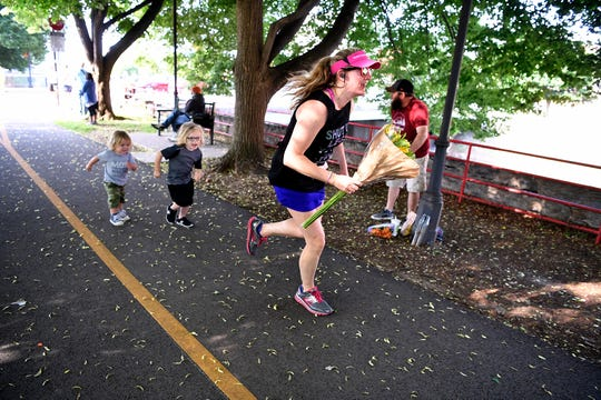 Shannon Walker of Dover heads to the finish line of the York Half Marathon with flowers in hand and her sons Auden, 2 left, and Callen, 4, in tow, Sunday, May 19, 2019. 