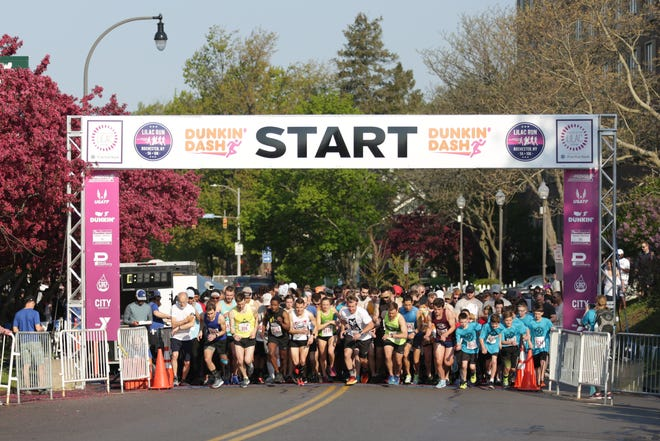 Runners take off at the start line of the Lilac Run 5k at Highland Park on Sunday, May 19, 2019.