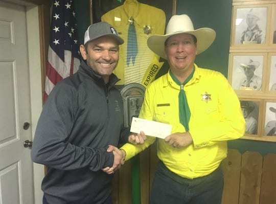 Scott Shoffner of Redding accepts a $200 check from Asphalt Cowboy Cameron Middleton for being the first to identify the Lone Stranger as Redding Vice Mayor Adam McElvain and his Sidekick as Rich Paulson, owner of Lulu's and Jack's Grill.