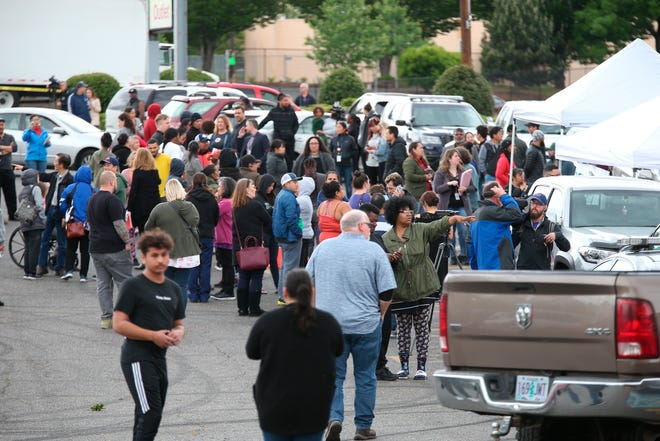 Students gather outside Parkrose High School  during a lockdown after a man armed with a gun was wrestled to the ground by a staff member, Friday, May 17, 2019 in Portland, Ore. The Portland Police Bureau said in a statement Friday that no shots were fired at Parkrose High School, no one was injured and the man is in custody. Police say there are no other suspects.