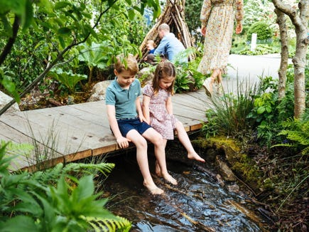 Prince George, 5, and Princess Charlotte, 4, dip their toes in a passing stream at the special garden their mom, Duchess Kate, created for the Chelsea Flower Show.