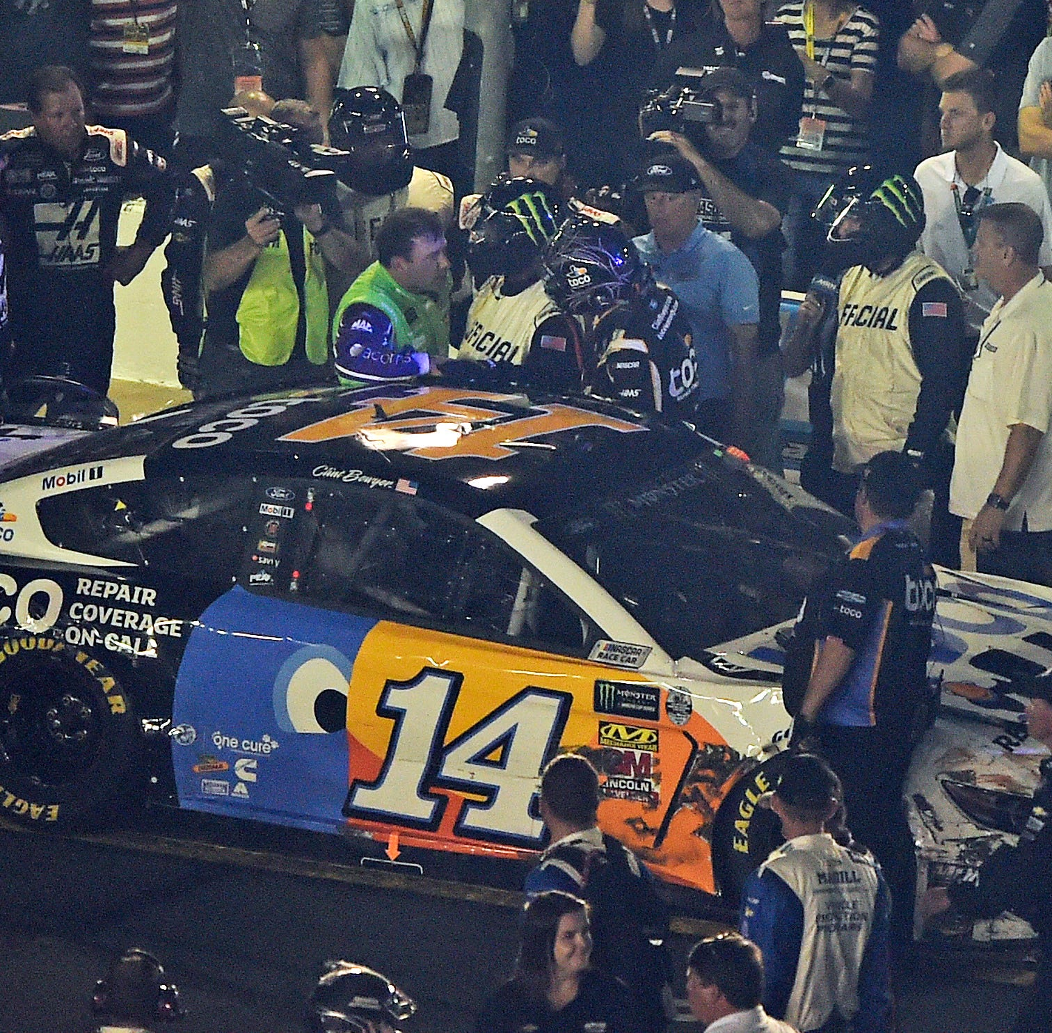 A NASCAR official tries to get between drivers Ryan Newman, left, and Clint Bowyer, right, after the NASCAR All-Star Race at Charlotte Motor Speedway.