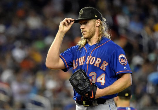 Mets starting pitcher Noah Syndergaard (34) tips his cap from the pitching mound in the seventh inning against the Marlins at Marlins Park.