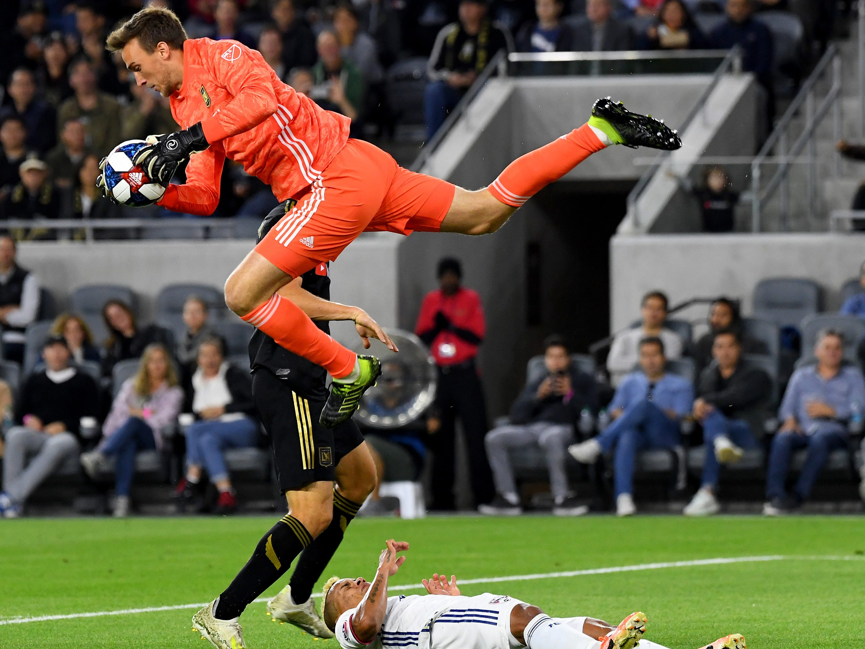 May 16: Los Angeles FC goalkeeper Tyler Miller leaps over FC Dallas midfielder Michael Barrios (21) while making a save on a shot on goal during the first half at Banc of California Stadium. LAFC won the game, 2-0.