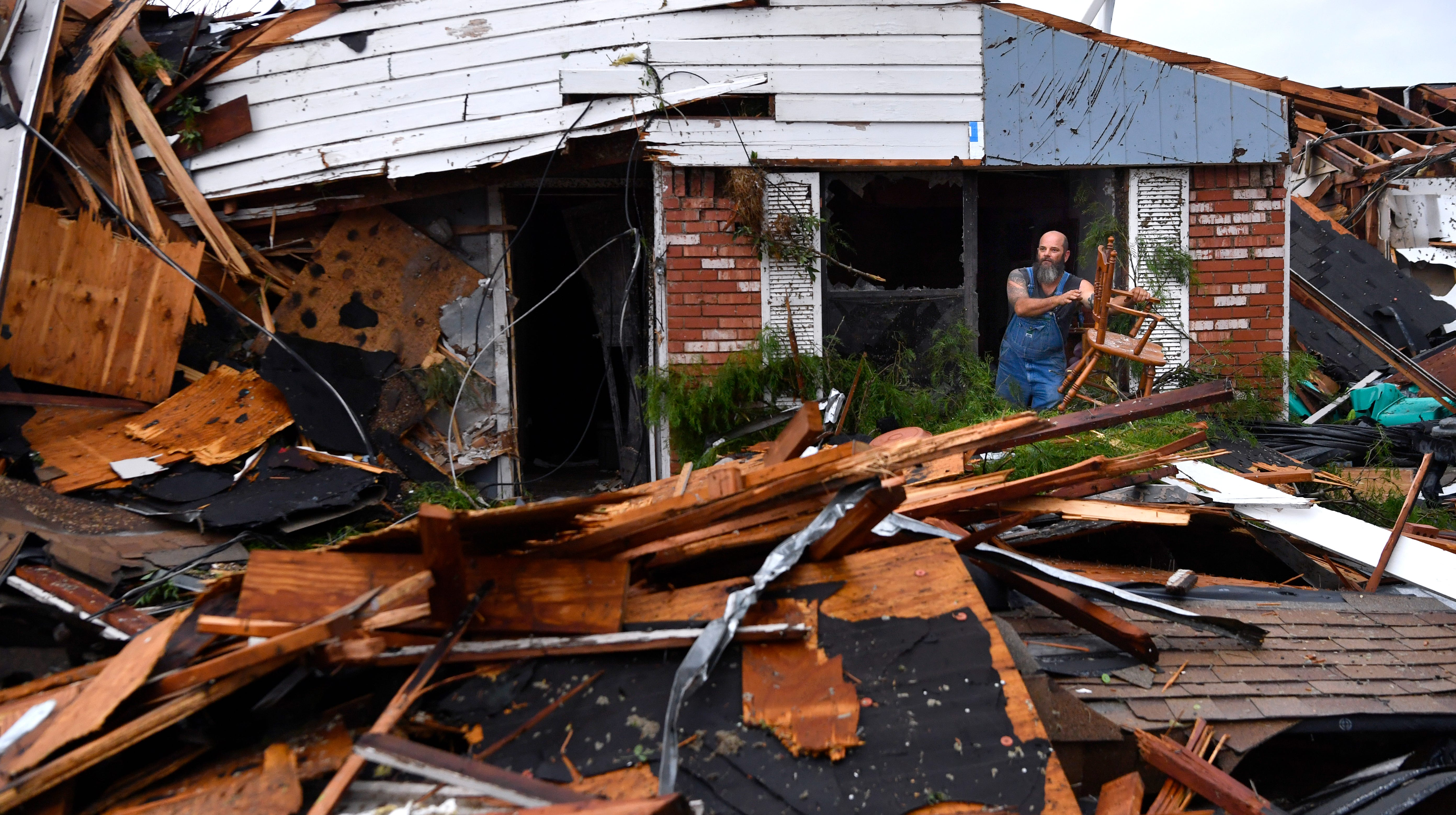 Wesley Mantooth lifts a wooden chair out a window of his father Robert's home after a possible tornado in Abilene on Saturday May 18, 2019.