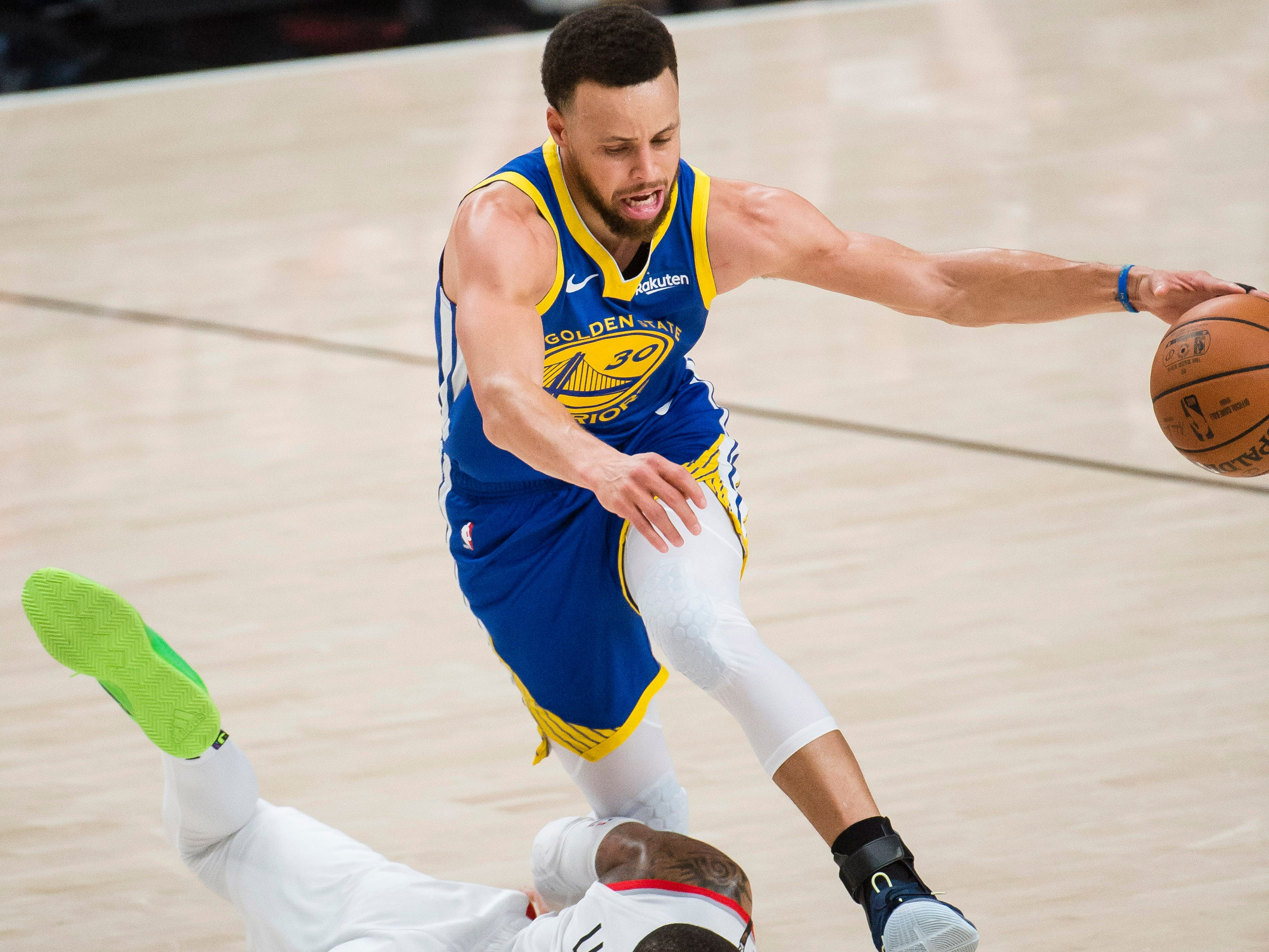 May 18: Warriors guard Stephen Curry (30) dribbles over fallen Blazers defender Damian Lillard (0) during Game 3 in Portland.