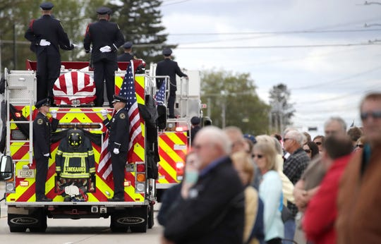 People gather along West Wisconsin Avenue during the funeral procession for Appleton firefighter Mitchell F. Lundgaard in May. Lundgaard was fatally shot after responding to a medical call at the Valley Transit Center in downtown Appleton.