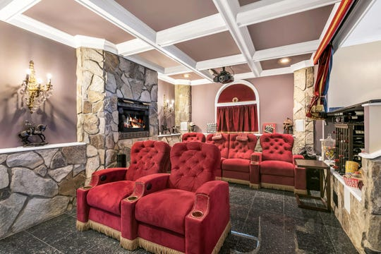 Sunken Movie Theater Room features coffered ceilings, recessed lighting, crystal sconces, and granite floors.