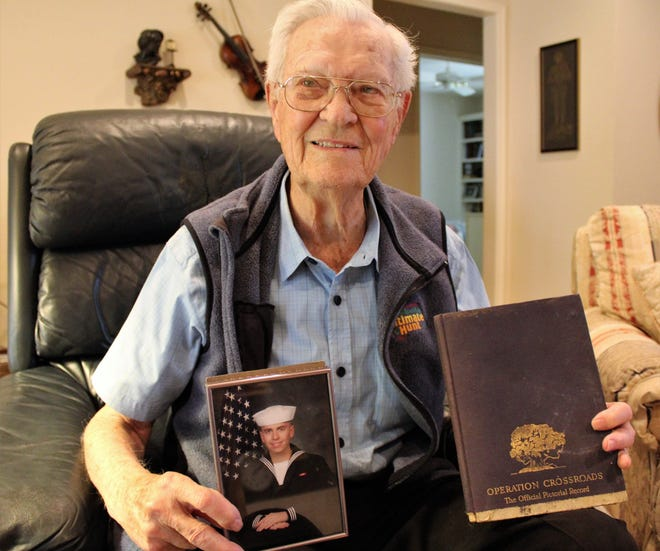 Dorman Farmer, now 93, in his home with a photo of his grandson, Rory Farmer, and a book that details the Bikini Atoll nuclear detonations, two of which he witnessed.