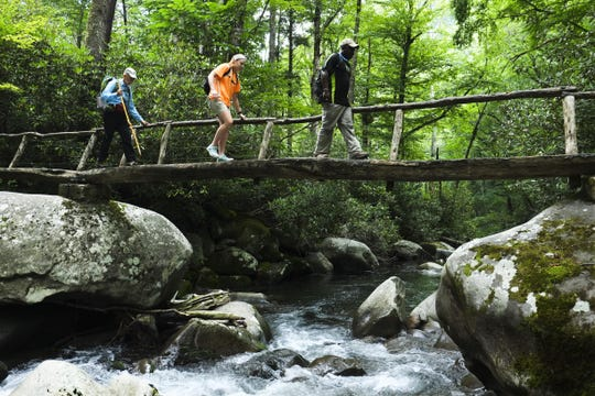 Great Smoky Mountains National Park Superintendent Cassius Cash walks with a group of students across a bridge in the park. The recent passage by the Senate of the Great American Outdoors Act would help to protect the park with funds for deferred maintenance.