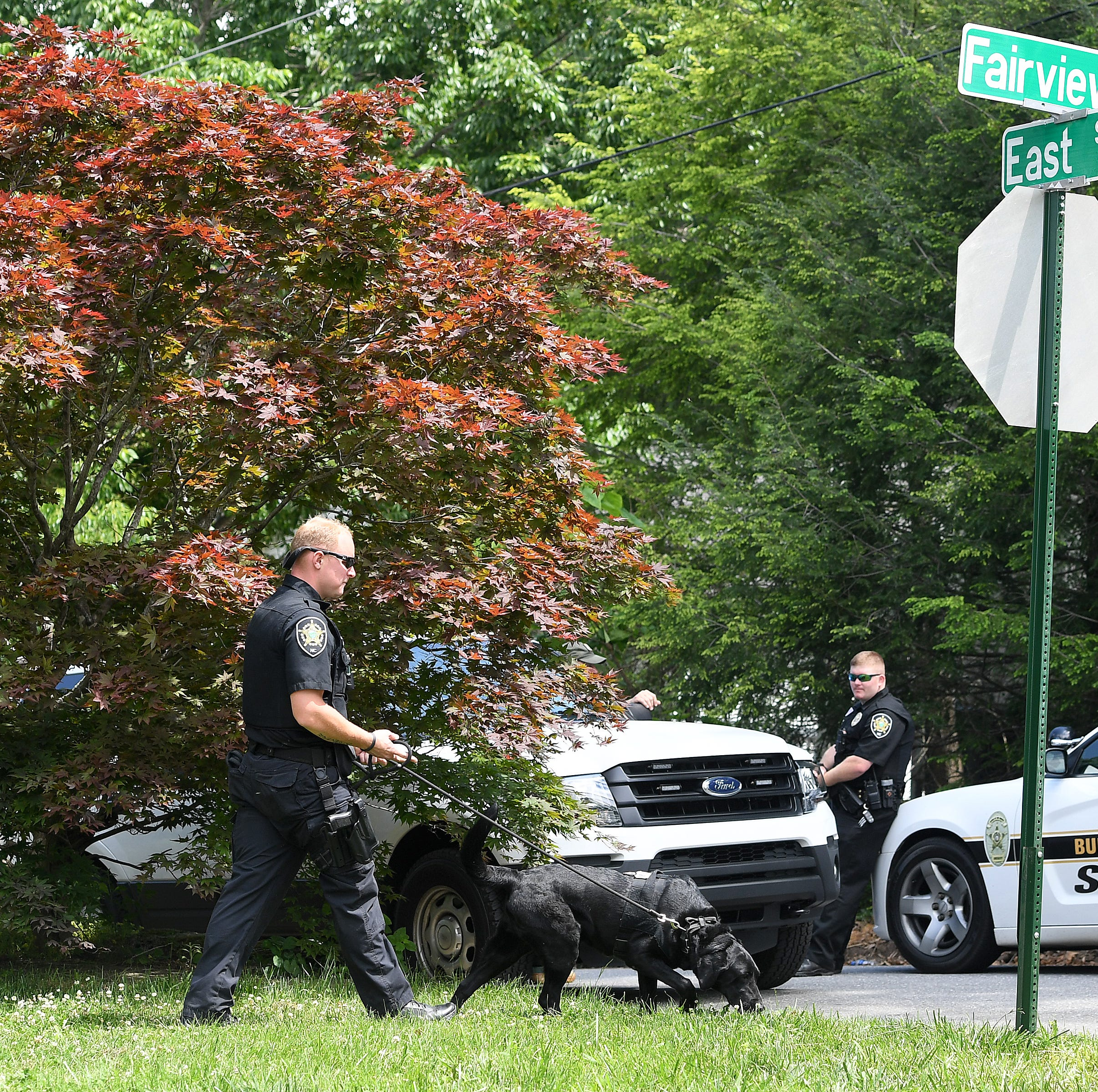 An officer walks a police dog at a scene on Fairview Road where three armed robbery suspects were apprehended after a pursuit on Fairview Road on May 20, 2019.