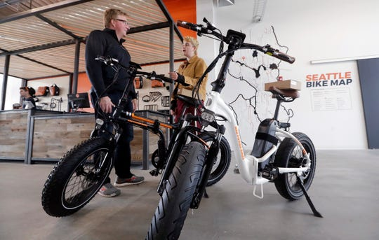 Customer Torre Treece, left, talks with Rad Power Bikes sales associate Becs Richards about the two electric bikes he bought at the shop in Seattle. The bicycle company said that they will absorb 100% of any tariff on their Chinese-made bicycles.