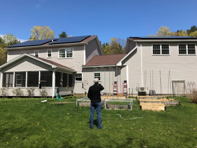 Mike Wheeler surveys his very energy efficient house, with solar panels, heat pumps, and Tesla Powerwalls.