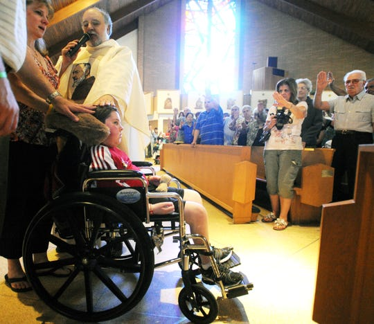 Christian Clopp, 9, of Mays Landing, is prayed for by the Rev. Pete Saparito and the congregation as his mother Joan looks on during the 9th annual St. Padre Pio Festival in 2011. Clopp died of an inoperable brain tumor in 2012.