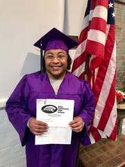Chae'Von Bowman receives her letter of completion from Dohn Community High School on the morning of April 29.