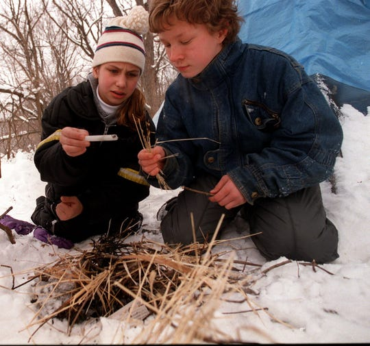 From 1997: Woodside Middle School seventh-graders Erika Hartung and Kevin Mihalovich attempt to start a fire during a wilderness survival test at the YMCA camp near Boone.