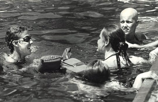 From 1984: Merry Coopman, left, and Kelisa Cress, far right, go for a swim at Camp-A-Panda at the YMCA camp near Boone.