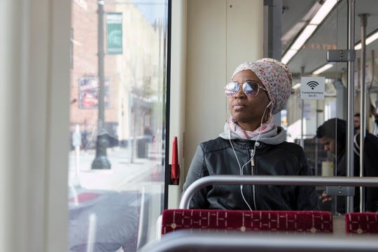 Julia Kapilango, of Dearborn, talks on her phone as she rides the QLINE in Detroit, Wednesday, May 8, 2019.