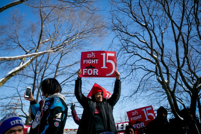 """Lisia Williams, 45, Clinton, Michigan, an organizer with """"Fight for 15"""" holds up a protest sign in Martin Luther King Memorial Park in the New Center in Detroit on February 12, 2018."""