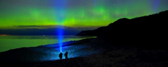 """Aurora Hunters,"" by Dale Niesen of South Rockwood,  was an Award of Excellence winner in the 2017 contest. Niesen used two LED flashlights, a wide angle lens and a 15-second exposure to create this shot of the northern lights near Empire Bluffs in  Sleeping Bear Dunes National Lakeshore."