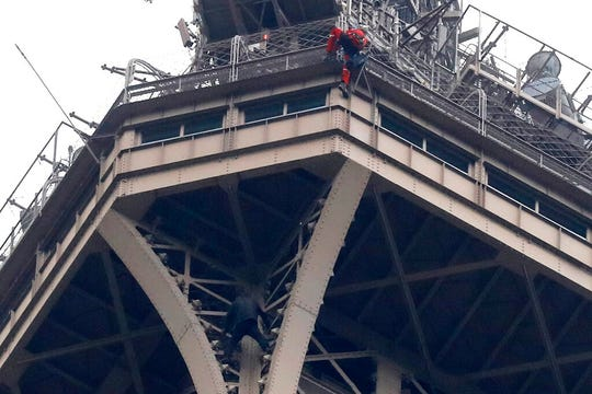 A rescue worker, top in red, decends the Eiffel Tower while a climber is seen below him between two iron columns Monday, May 20, 2019 in Paris.