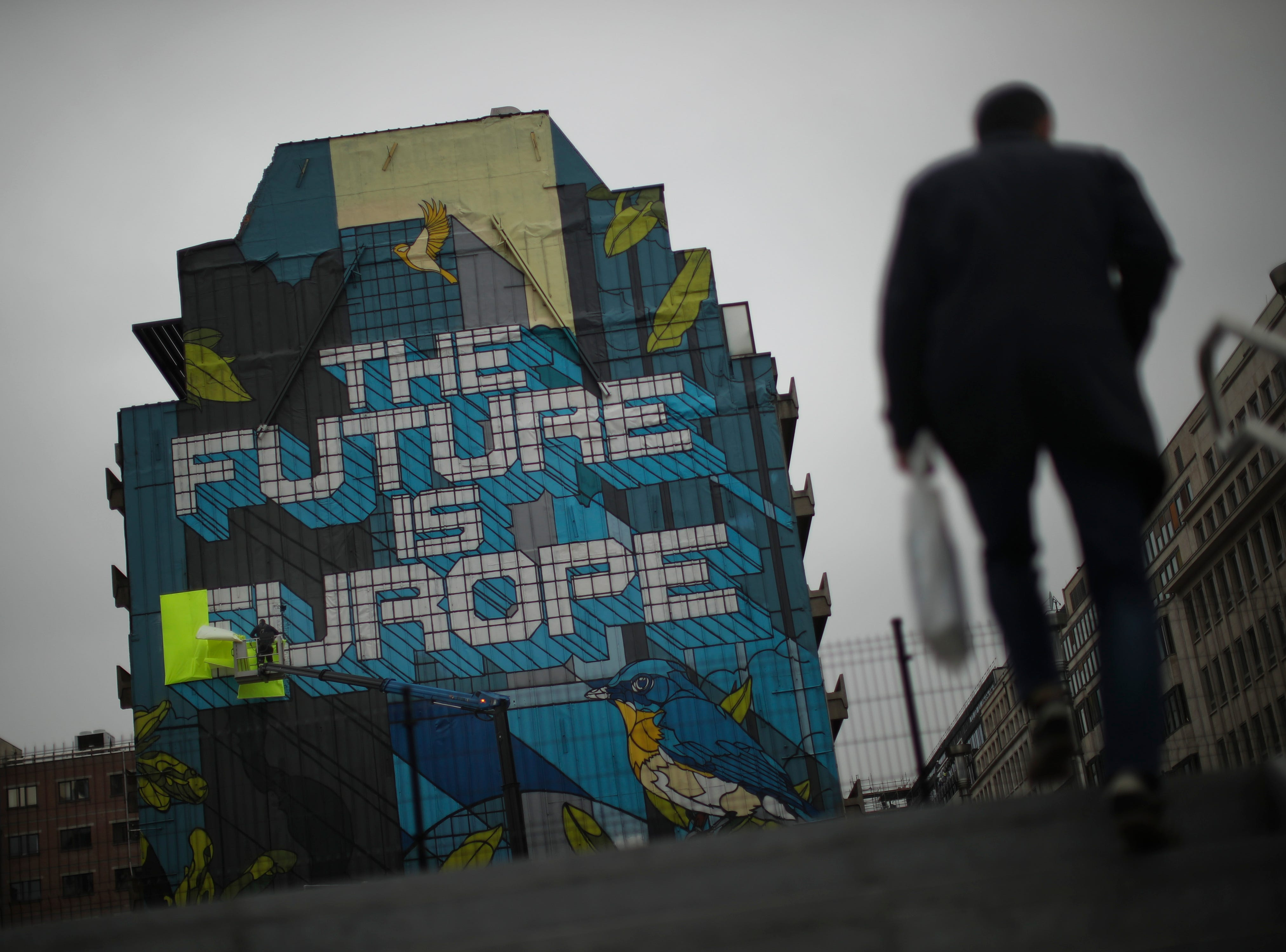 """A worker removes yellow banners, placed by supporters of the """"yellow vest"""" movement, that covered the word """"Europe"""" of a large graffiti for a few days in Brussels, Monday, May 20, 2019. Some 400 million Europeans from 28 countries will head to the polls May 23-26 to choose lawmakers to represent them at the European Parliament for the next five years."""