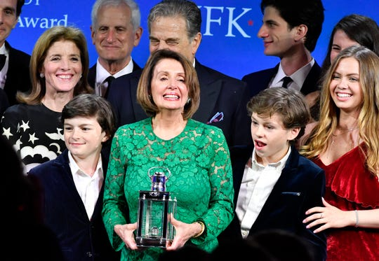 Speaker of the House Nancy Pelosi, D-Calif., center, stands with family, including her grandchildren Thomas Vos, left, and Paul Vos, right, as she receives the 2019 John F. Kennedy Profile in Courage Award, Sunday.