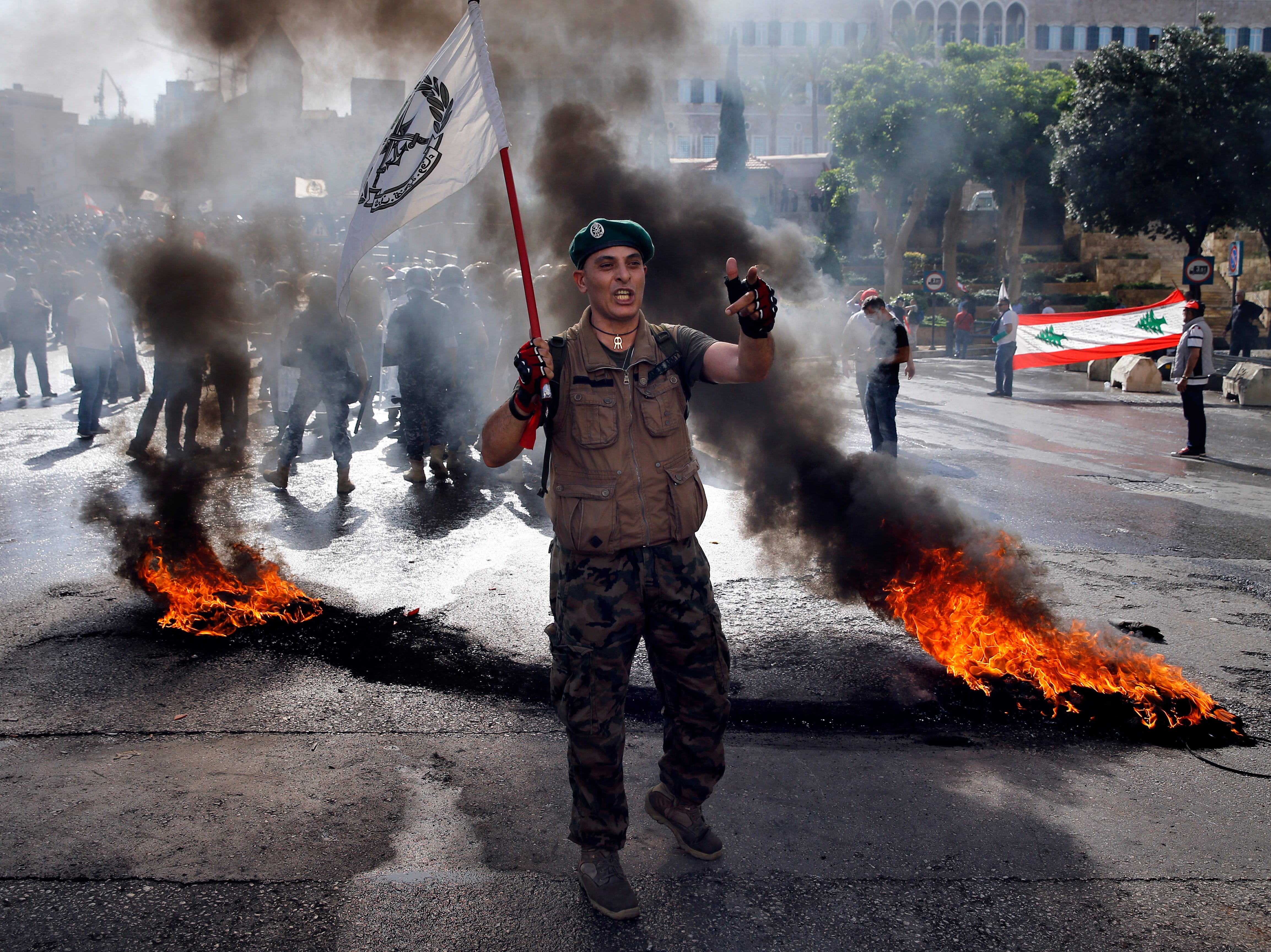 """A retired Lebanese soldier chants slogans while holding an army flag during a protest in Beirut, Lebanon, Monday, May 20, 2019, as the government faces a looming fiscal crisis. Over a hundred protesters gathered Monday in downtown Beirut shouting """"Thieves, thieves!"""" as the Cabinet met for its 16th session to reach agreement on controversial budget cuts."""
