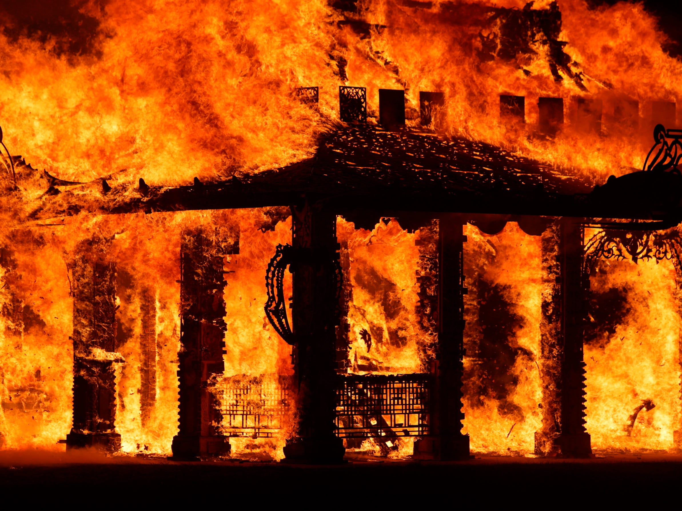 """The """"Temple of Time"""" built as a memorial to the 17 victims of a shooting at Marjory Stoneman Douglas High School is seen on fire during a ceremonial burning in Coral Springs, Fla., Sunday, May 19, 2019. The """"Temple of Time"""" public art installation was set on fire Sunday at the ceremony hosted by the cities of Parkland and Coral Springs, where the high school's students live."""