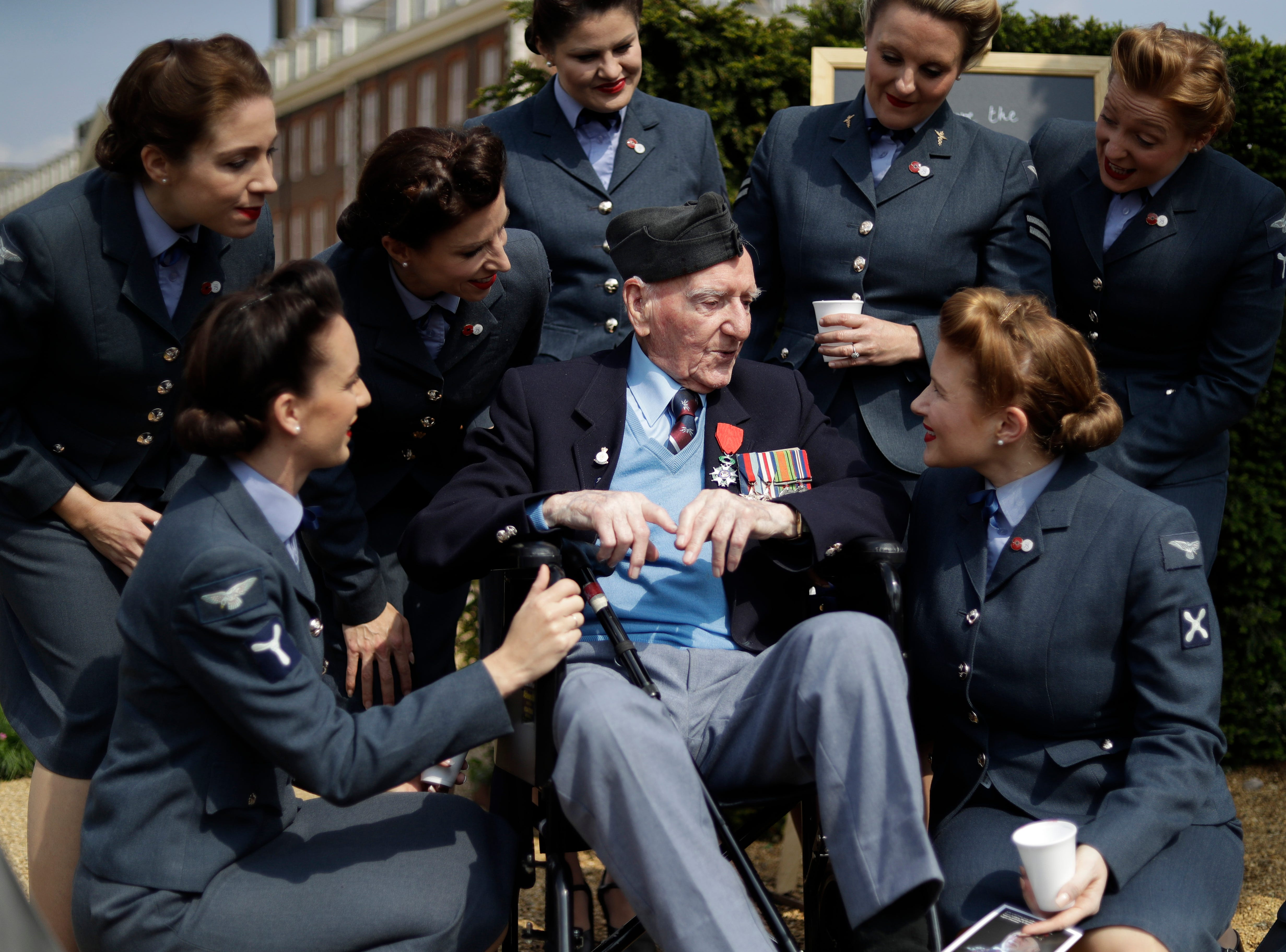 """World War II British D-Day veteran Bernard Morgan, aged 95, who was a sergeant decoder in the Royal Air Force 83 Group Control Centre and landed at Gold beach on the afternoon of June 6, 1944, speaks to the 'D-Day Darlings' singing group after they posed for a group photograph on the """"D-Day 75 Garden,"""" for the 75th anniversary of D-Day at the RHS (Royal Horticultural Society) Chelsea Flower Show, in London, Monday, May 20, 2019. World-renowned and quintessentially British, the annual show is a celebration of horticultural excellence and innovation."""
