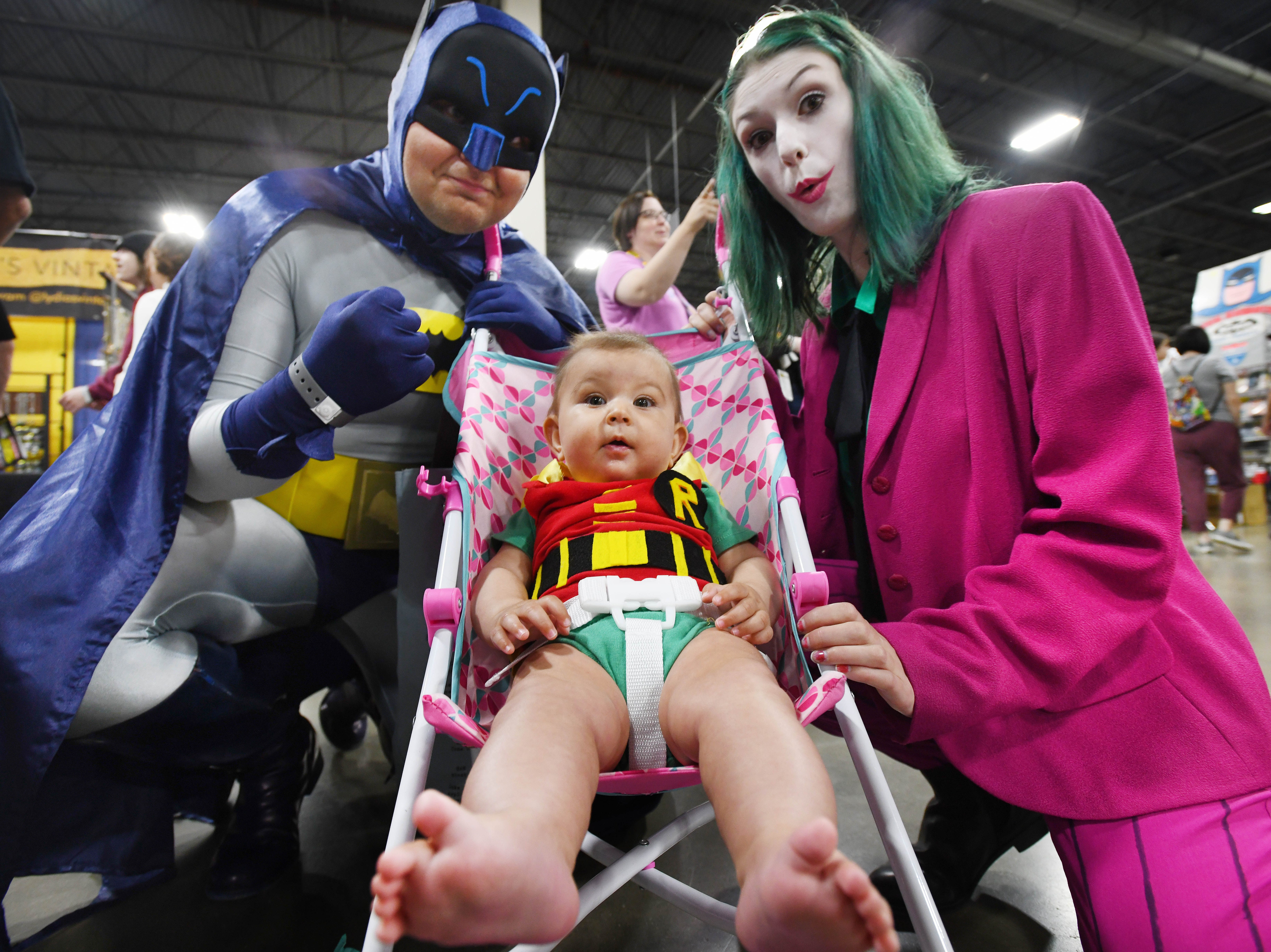 Tim Parrelly with wife Ehlana Parrelly and daughter Ellie Parrelly, 5 months, look the part in classic Batman, Robin and the Joker outfits at Motor City Comic Con at Suburban Collection Showcase  in Novi, Michigan on May 17, 2019.