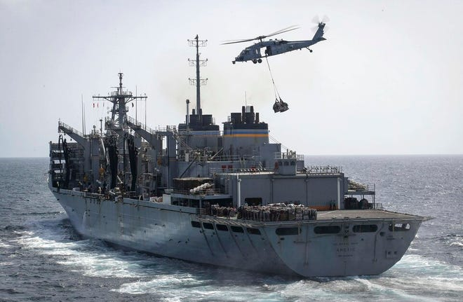 """In this Sunday, May 19, 2019, photo released by the U.S. Navy, an MH-60S Sea Hawk helicopter from the """"Nightdippers"""" of Helicopter Sea Combat Squadron 5 transports cargo from the fast combat support ship USNS Arctic to the Nimitz-class aircraft carrier USS Abraham Lincoln during a replenishment-at-sea in the Arabian Sea."""