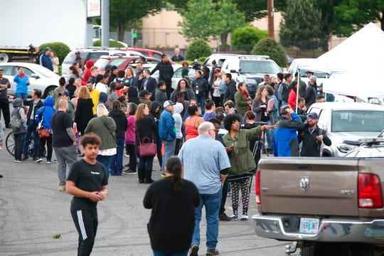Students gather outside Parkrose High School  during a lockdown after a man armed with a gun was wrestled to the ground by a staff member, Friday, May 17, 2019 in Portland, Ore.