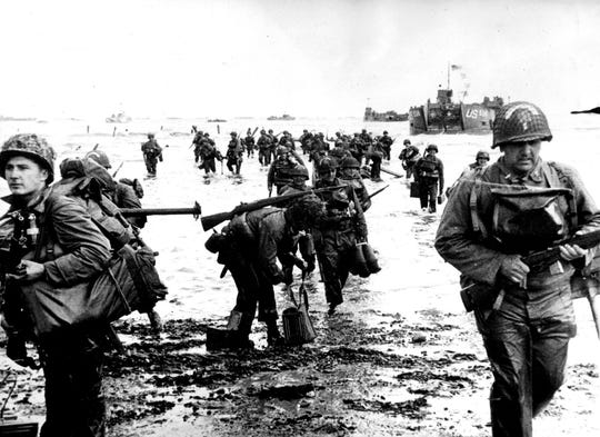 American troops loaded with equipment wade ashore in Normandy, France on June 8, 1944, and make for their assembly point. Units of the invasion fleet lie off shore all along the coast.